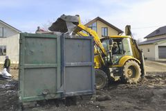 A big yellow tractor loads construction garbage into a container with a bucket stock photos