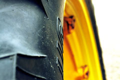 Big yellow tractor rim. Abstract blurry close up of nice contrast of two colors Stock Photos