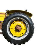 Big Yellow Tractor Tire. Vertical close-up shot of a big yellow tractor tire on a white background Stock Photography