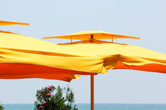 Big yellow umbrellas at the seaside Royalty Free Stock Photos
