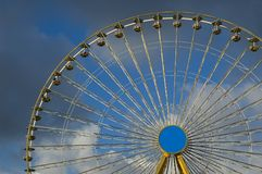 Big yellow wheel at the local fair. Against blue cloudy background Royalty Free Stock Images