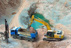 Big yellow wheel work in a quarry. Yellow excavator loading stones in a truck Stock Image