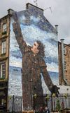 Big yin reaching for the roof. The Scottish comedian Billy Connolly. A painting on a wall celebrating his 70th Birthday, in Glasgow Scotland Royalty Free Stock Photos