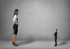 Big young businesswoman standing in front of small businessman Royalty Free Stock Photography