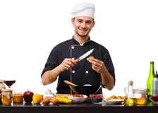 A big young guy, the chef, breaks the egg with a knife royalty free stock photo