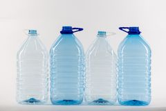 Bigger size clear water bottles standing in right row. Plastic water bottles. Bigger size clear water bottles standing in right row as an example of extra waste stock photo