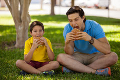 The biggest bite wins!. Young father and his son giving a big bite to their hamburgers while eating at a park royalty free stock images