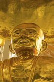 Biggest golden statue of monk. The golden statue of monk in the temple of Thailand Royalty Free Stock Photography