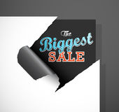 The Biggest Sale text uncovered from teared paper corner. Stock Photo