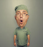Bighead amazed doctor in uniform. Over grey background Stock Images