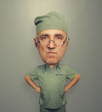 Bighead angry doctor in glasses. Funny picture of bighead angry doctor in glasses over dark background Stock Image