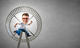 Bigheaded man. Funny picture of running in wheel man with big head over cement background Royalty Free Stock Photo