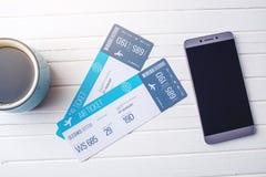 Biglietti aerei, telefono e computer portatile della tazza di caffè su fondo di legno bianco Concetto di acquisto della prenotazi immagini stock libere da diritti
