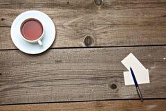 Biglietti da visita in bianco con la tazza di tè e della penna sopra Immagini Stock