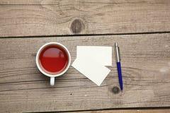 Biglietti da visita in bianco con la tazza di tè e della penna sopra Immagini Stock Libere da Diritti