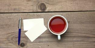Biglietti da visita in bianco con la tazza di tè e della penna sopra Immagine Stock