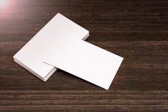Biglietti da visita in bianco isolati su un fondo di legno scuro Fotografie Stock Libere da Diritti