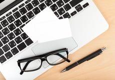 Biglietti da visita in bianco sopra il computer portatile sulla tavola dell'ufficio Immagine Stock Libera da Diritti