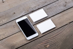Biglietti da visita e smartphone isolati su vecchio fondo di legno Immagine Stock Libera da Diritti