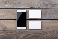 Biglietti da visita e smartphone isolati su vecchio fondo di legno Fotografia Stock