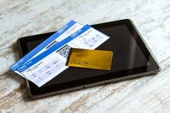 Biglietti di linea aerea d'acquisto su una compressa Fotografia Stock