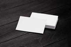 Biglietto da visita in bianco e pila di identità corporativa su fondo di legno alla moda nero con sfuocatura, modello fotografie stock