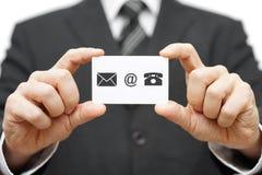 Biglietto da visita della tenuta dell'uomo d'affari con il email, posta, icona del telefono continuazione Immagine Stock