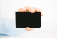Biglietto da visita nero vuoto in bianco che tiene a mano Fotografia Stock Libera da Diritti