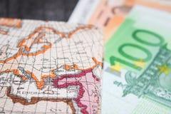 Biglietto di aeroplano, dei soldi e mappa Eurobanknotes con il passaggio e la mappa di imbarco, su fondo di legno nero Fotografia Stock