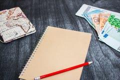 Biglietto di aeroplano, dei soldi, mappa e taccuino Eurobanknotes con il passaggio di imbarco, la mappa e la matita rossa su fond Fotografie Stock Libere da Diritti