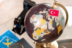 Biglietto di aeroplano e bandiera del turco sul globo immagini stock libere da diritti