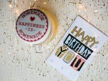 Biglietto di auguri per il compleanno felice su una tavola e sulle luci di Natale Immagine Stock