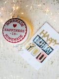 Biglietto di auguri per il compleanno felice su una tavola e sulle luci di Natale Immagine Stock Libera da Diritti