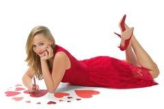 Biglietto di S. Valentino di menzogne dei cuori rossi biondi della donna isolato Fotografia Stock