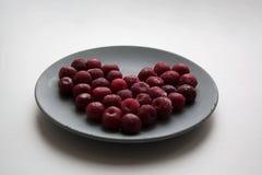 Biglietto di S. Valentino rosso del cuore delle ciliege sul piatto immagini stock