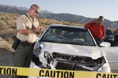 Biglietto di scrittura del poliziotto per un incidente con l'uomo sulla chiamata Immagine Stock