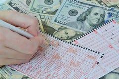 Biglietto e matita di lotteria sul fondo del dollaro Fotografia Stock