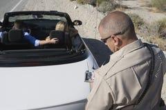 Biglietto maturo di scrittura del poliziotto di traffico Fotografia Stock