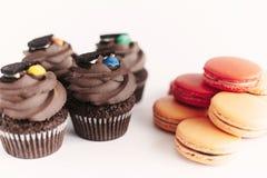 Bigné alla moda del cioccolato con il biscotto e la caramella sulla cima e sul colo Fotografia Stock