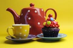 Bigné colorato luminoso della caramella con la teiera e la tazza del pois. fotografie stock