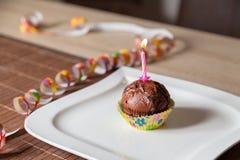 Bigné con una candela di compleanno sul piatto Fotografia Stock
