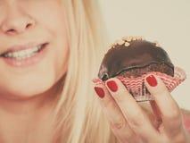 Bigné del cioccolato della tenuta della donna circa al morso fotografia stock