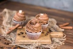 Bigné del cioccolato e bastoni saporiti di cannella su un bordo di legno Front View immagine stock