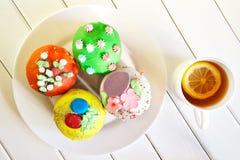 Bigné deliziosi e variopinti - dolci di Pasqua su un piatto bianco e una tazza di tè con una fetta di limone Prima colazione del  fotografie stock