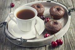 Bigné della ciliegia e tazza di tè su un vassoio di legno Immagini Stock