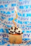 bigné di buon compleanno di pepita di cioccolato con la candela ondulata arancio Fotografie Stock Libere da Diritti