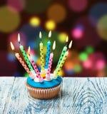 Bigné di compleanno con le candele brucianti Immagini Stock