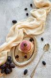 Bigné dorato porpora con la mora sul vassoio d'annata d'argento decorato con il cucchiaio lungo, panno marrone chiaro, uva blu fr Fotografia Stock