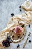 Bigné dorato porpora con la mora sul vassoio d'annata d'argento decorato con la forcella del dessert, panno marrone chiaro, ramo  Immagine Stock