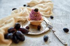 Bigné dorato porpora con la mora sul vassoio d'annata decorato con la forcella, il panno leggero, l'uva blu fresca e le more Immagini Stock